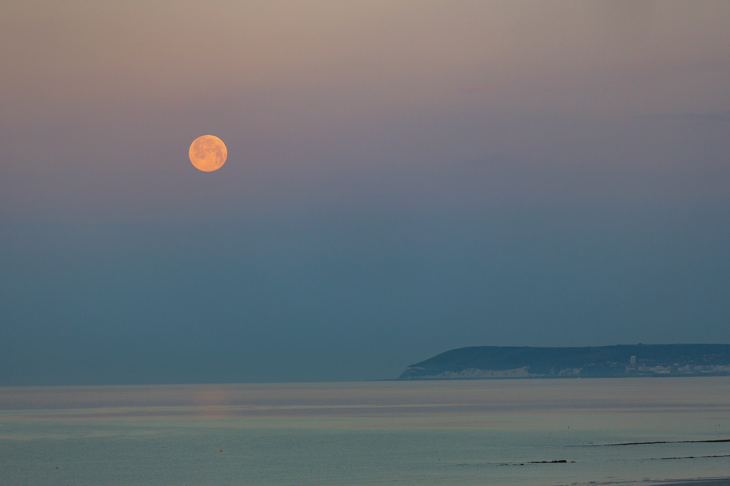A luminous full moon hovers over the sea cliffs at Beachy Head