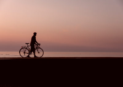 Walking my bicycle along a jetty at Bexhill-on-Sea, silhouetted by the pre-dawn glow in the sky