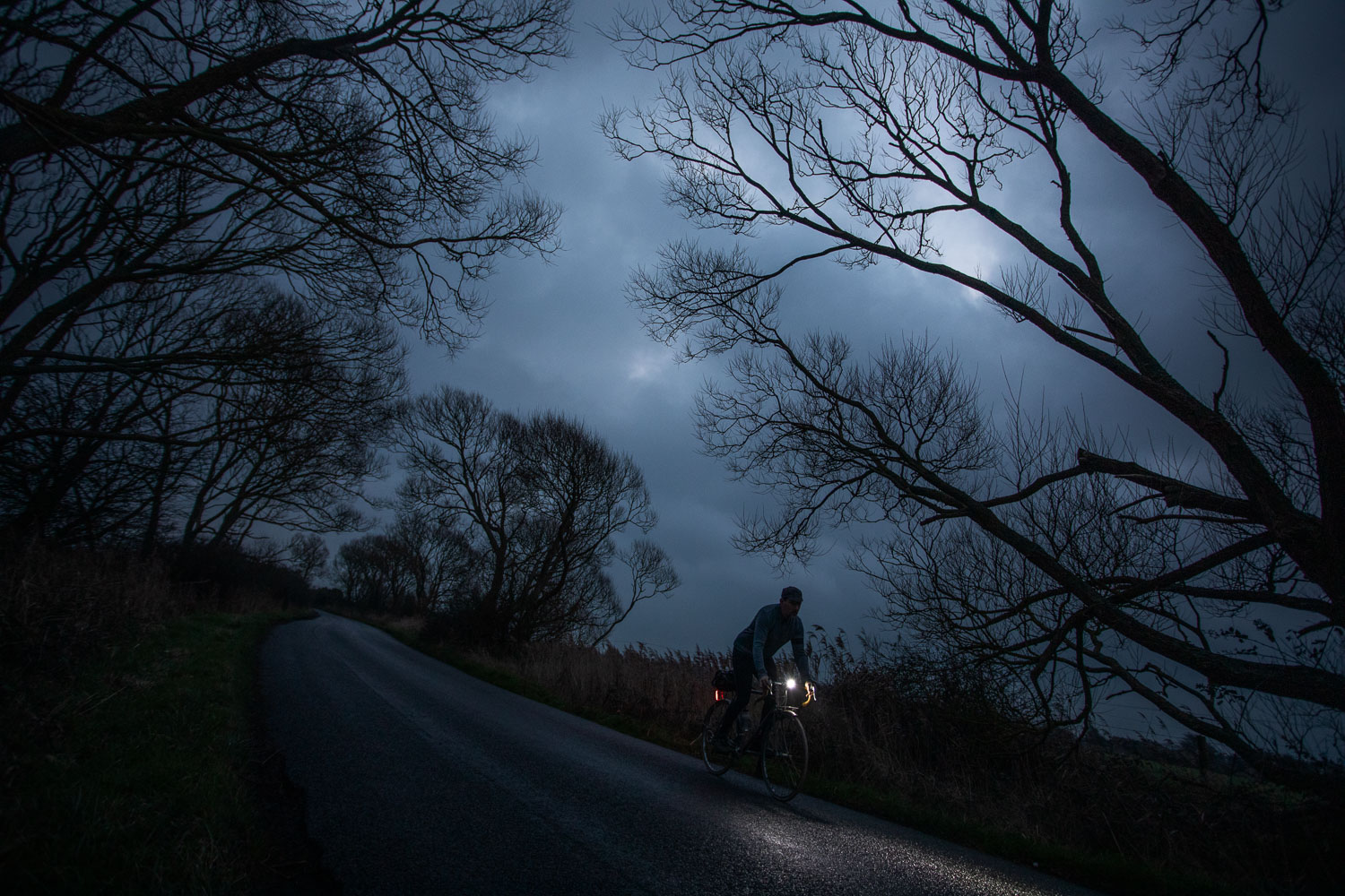 cyclist with headlamp pedals along a darkened moonlit lane in Sussex