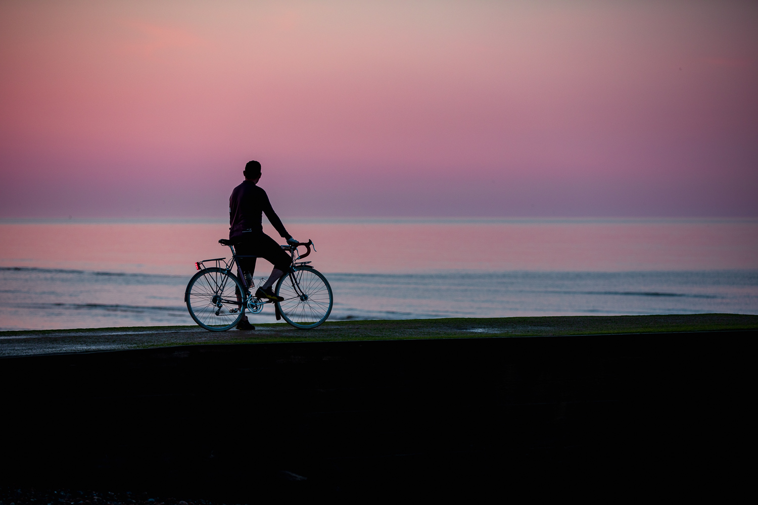 Cycling in Sussex - a cyclist in silhouette looks towards a violet sunrise on the seafront at Bexhill-on-Sea