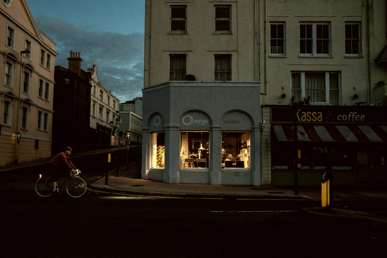 Nighthawk - A Bouquet to Edward Hopper. A cyclist pedals past a dark urban street corner l