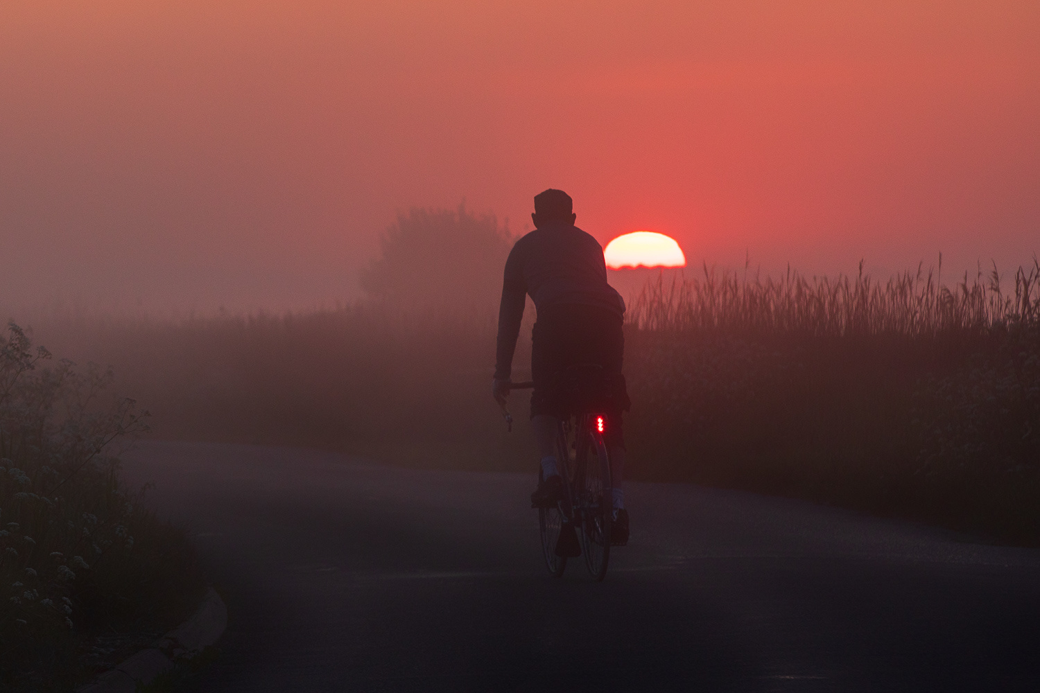 Red Sun in Morning - cyclist looking at glowing red sun rise