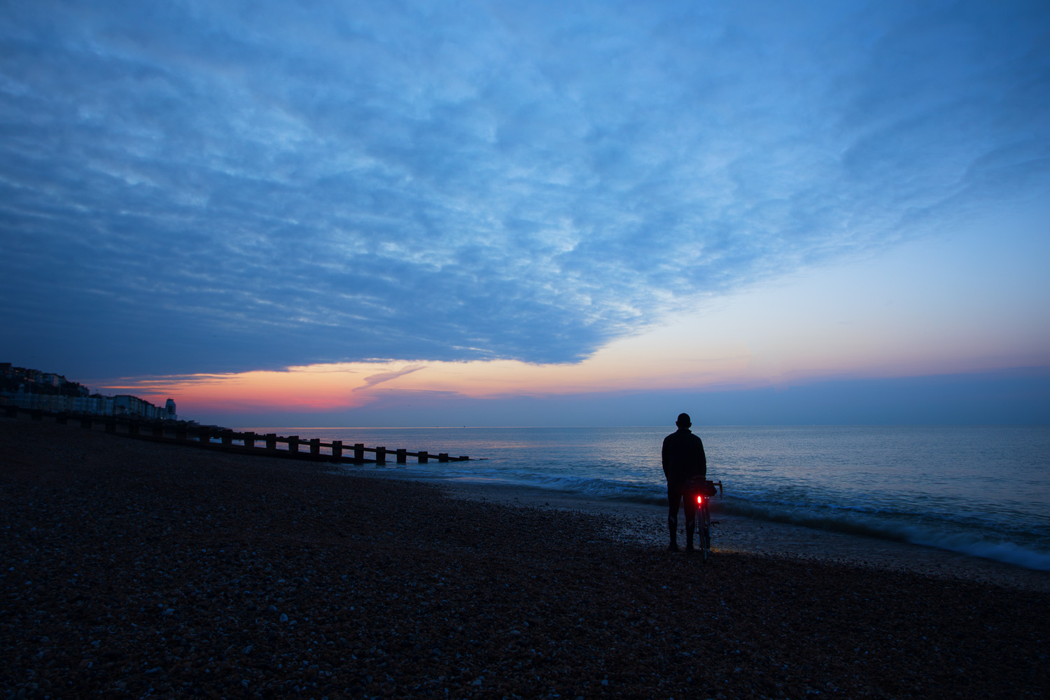 Man with bicycle standing on beach in pretty light just before dawn