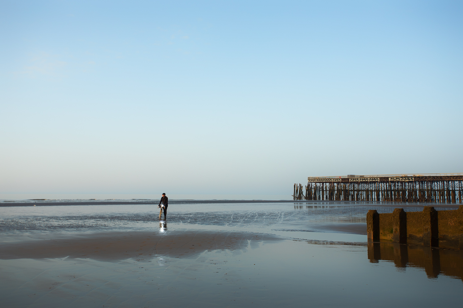 Man walking bicycle across low tide sands at dawn old pier in background