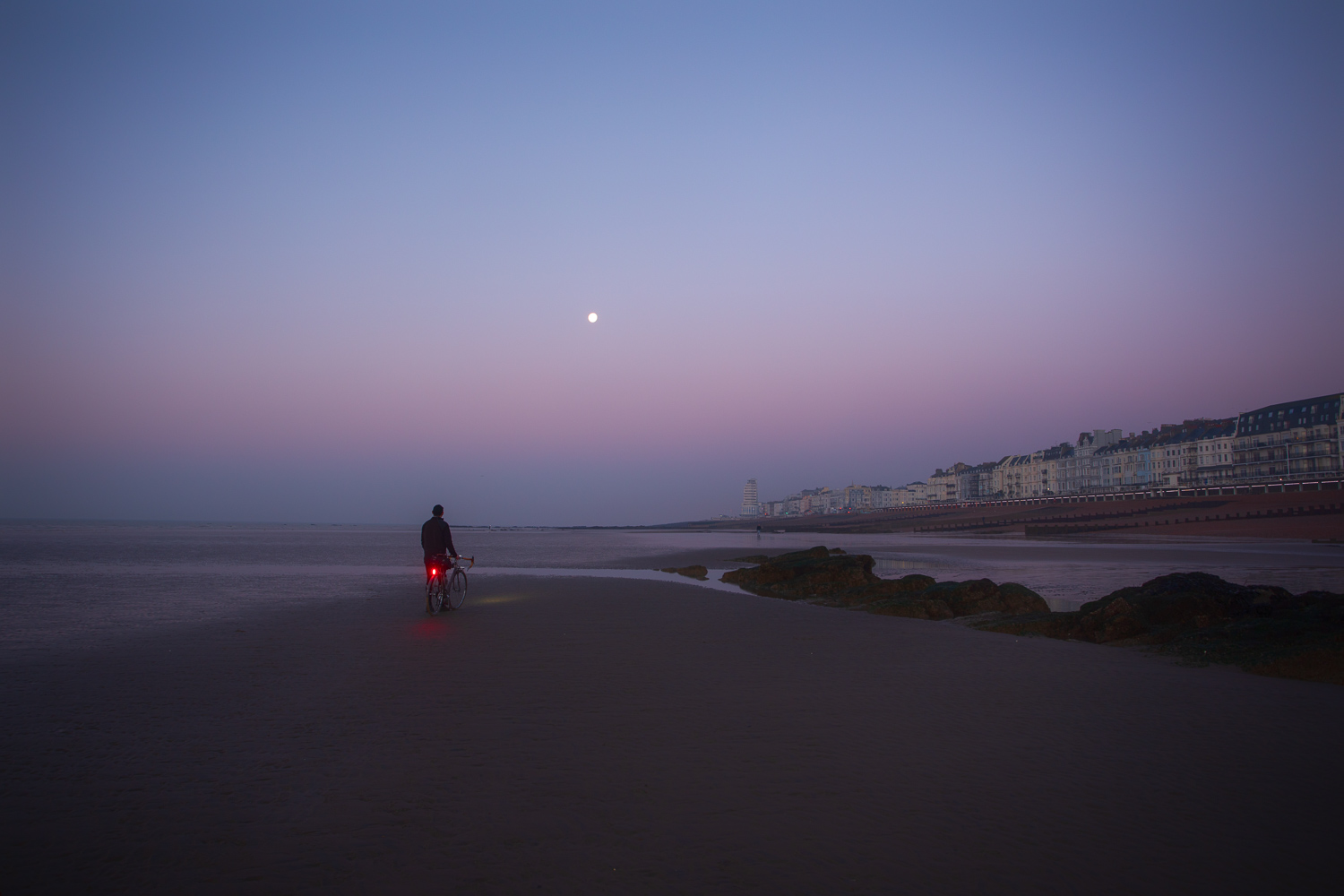 Man with bicycle standing on tidal flat looking at moon over town of Hastings