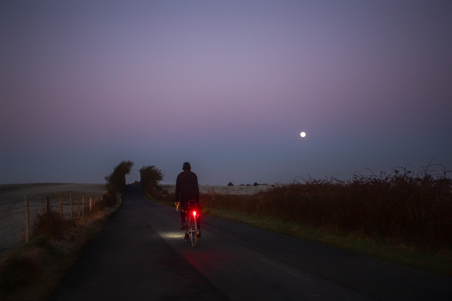 Cyclist pedalling along dark country lane with moon in the sky taillight glowing