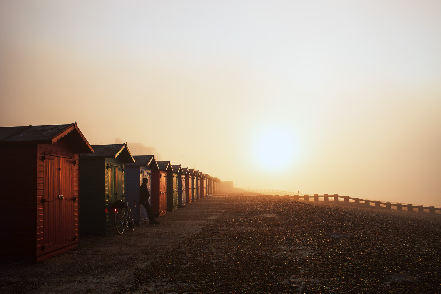Man with bicycle leaning against row of beach huts at sunrise