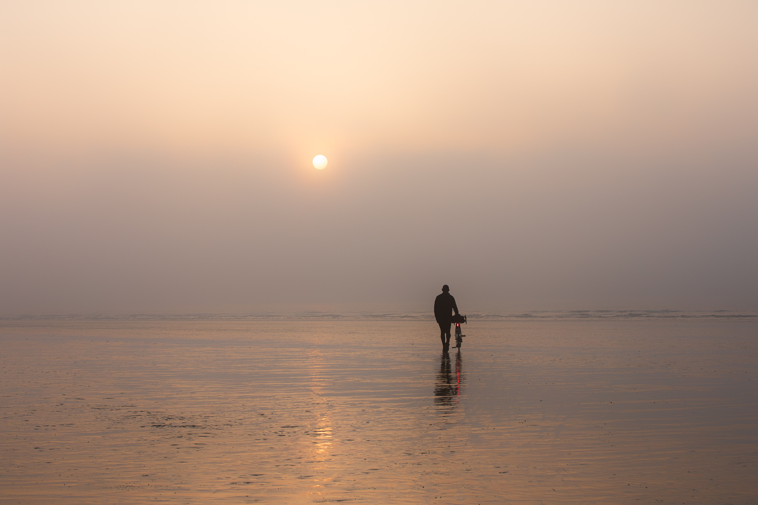 Man with bicycle walking into misty sunrise on shimmering sands