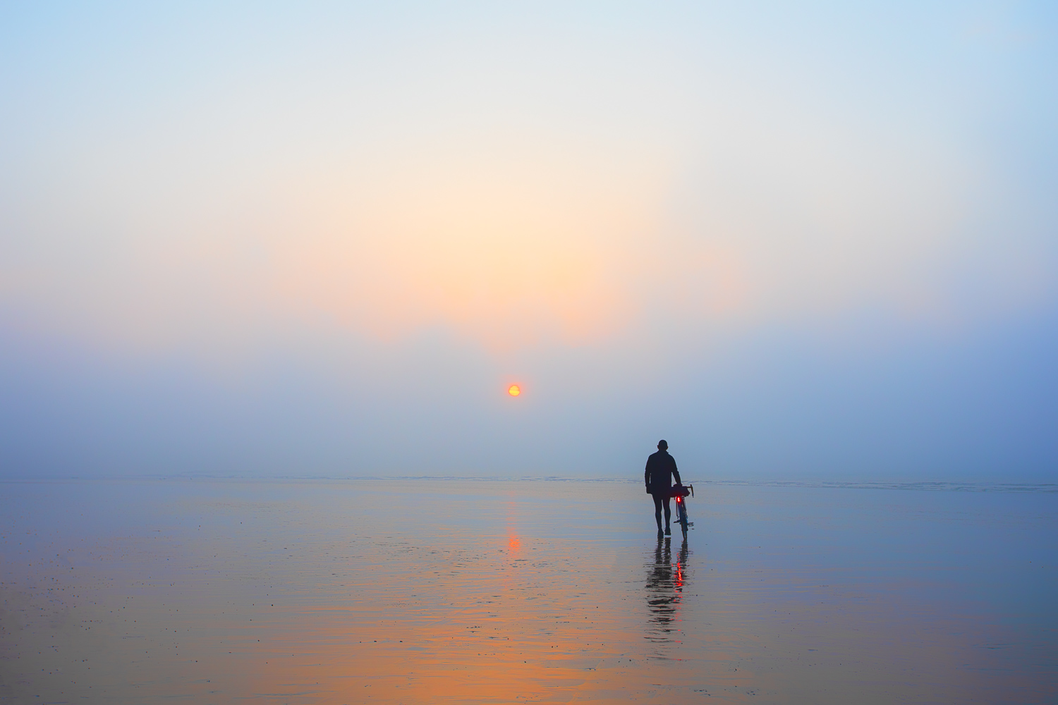 Man with bicycle walking towards misty sunrise on a shimmering sandy beach