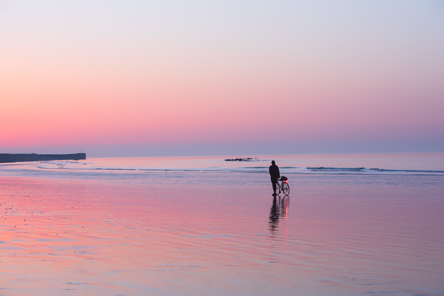 Man with bicycle standing on shimmering pink low tide sand at sunrise