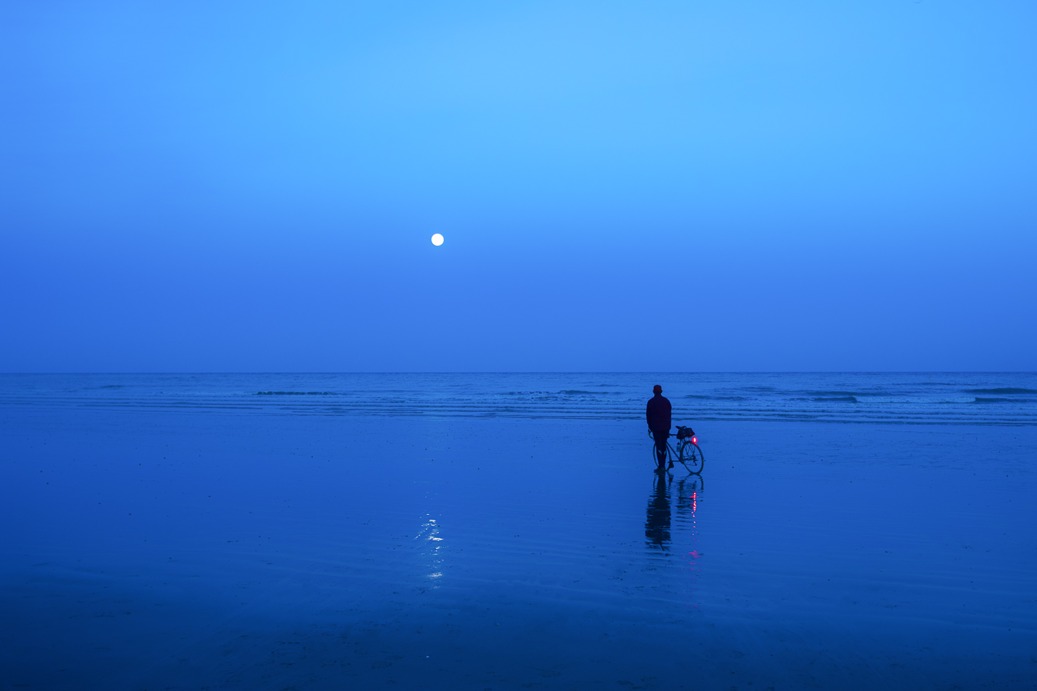 Silhouette of man with bicycle gazing at full moon on a shimmering beach
