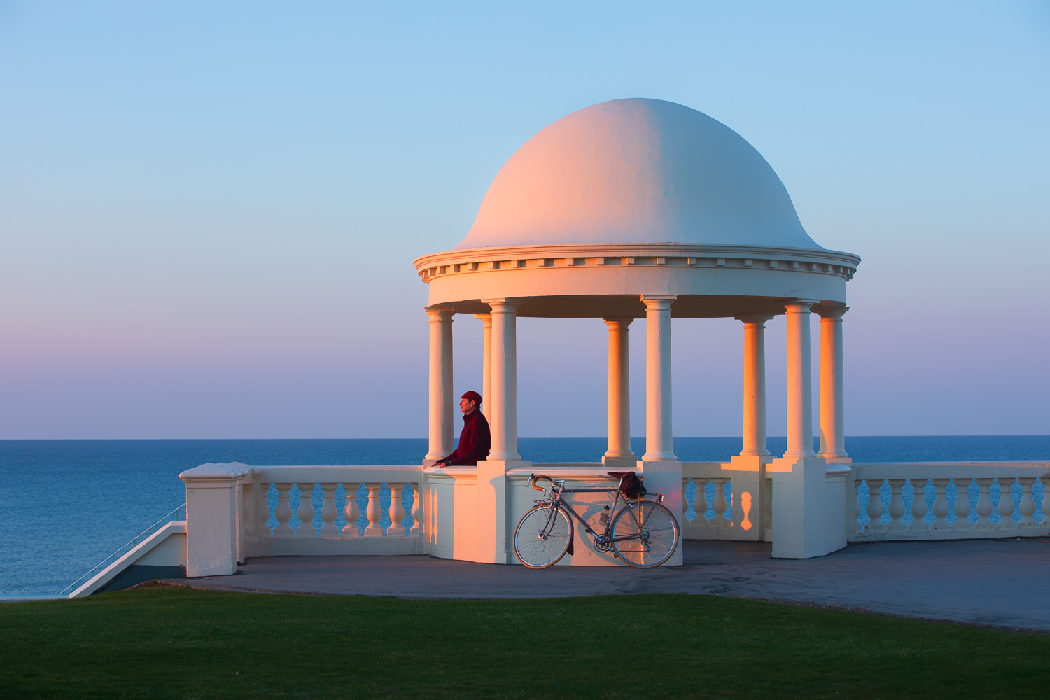 Man standing beneath classical dome by seaside looking at sunrise
