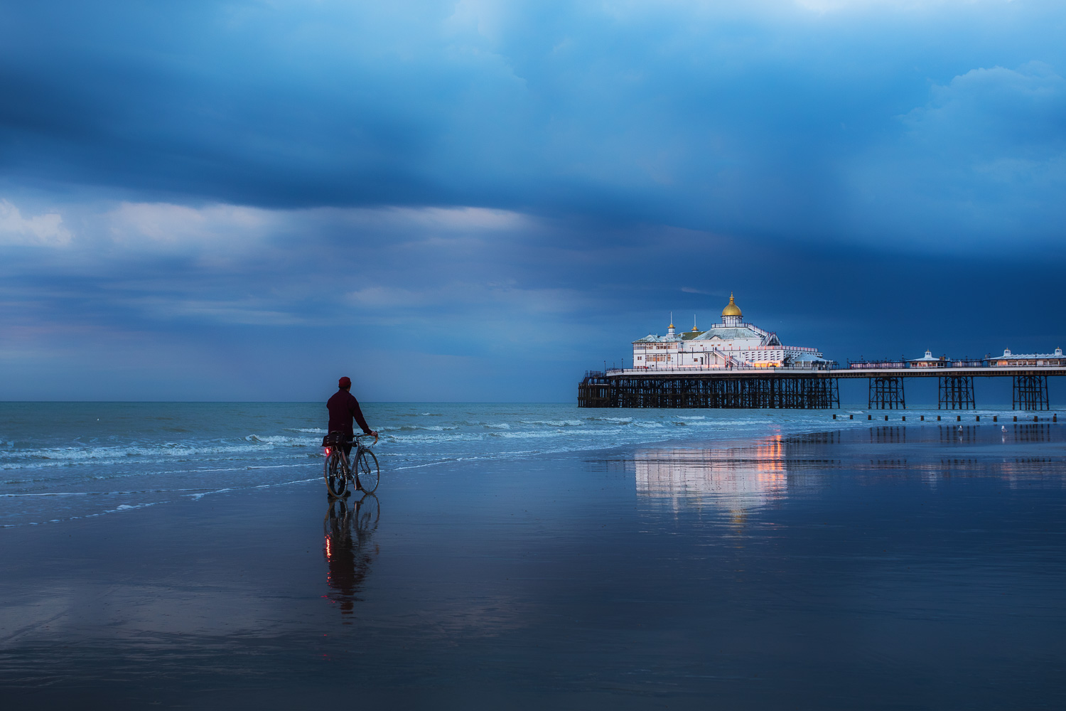 Man with bicycle gazing at Eastbourne pier stormy sky