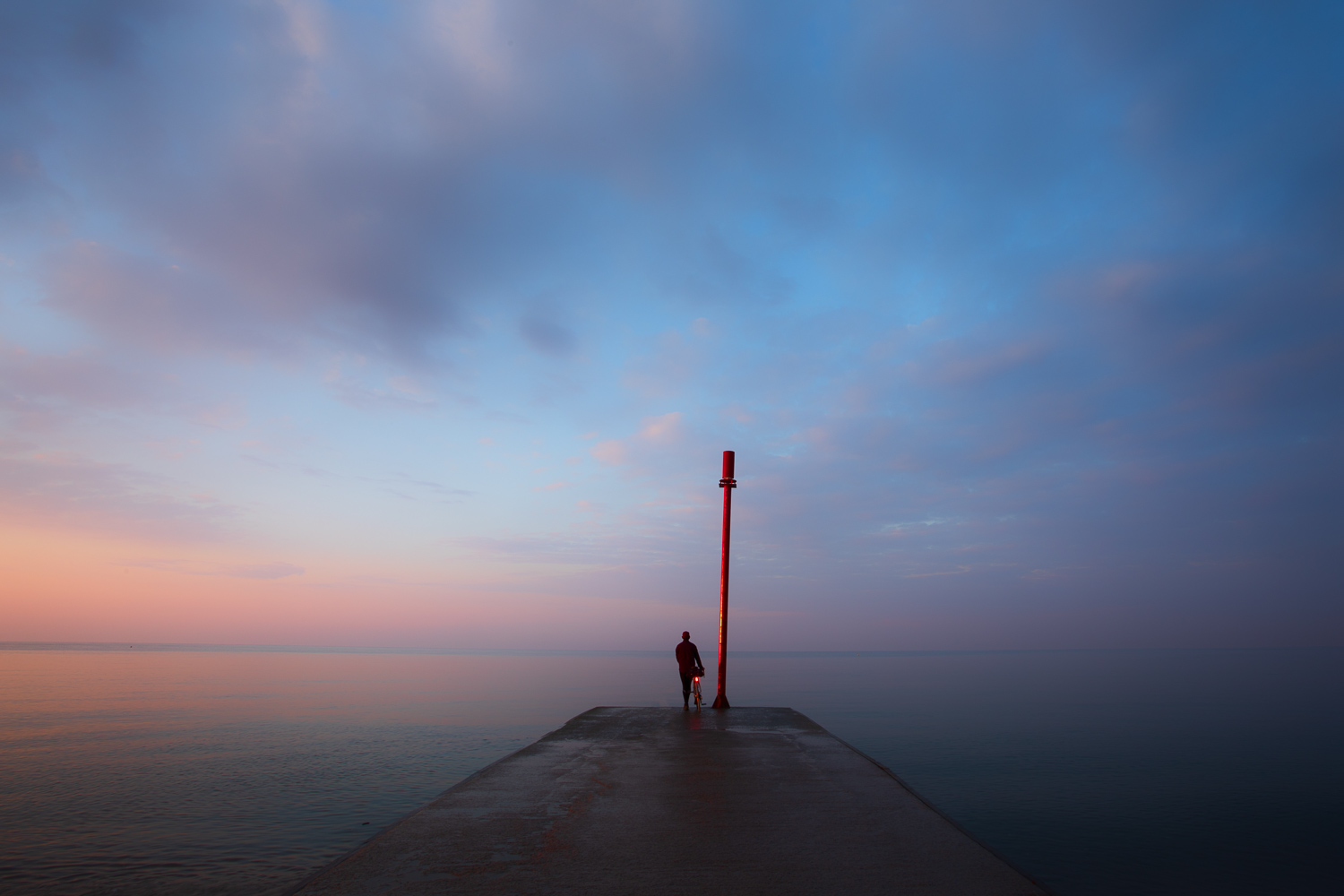 Man with bicycle at end of pier at sunrise