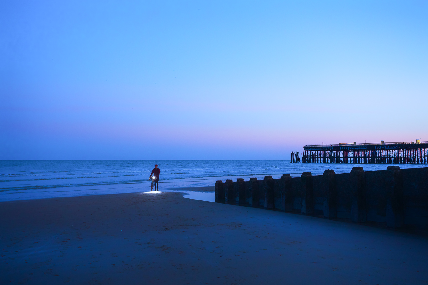 Man walking bicycle on beach at dusk, headlight glowing, pier in background