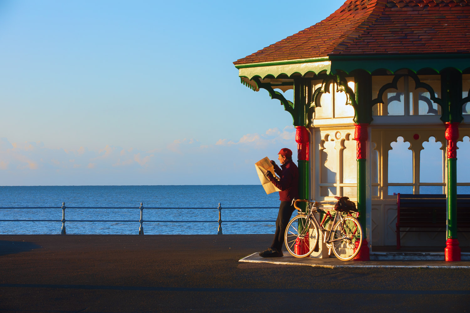 Man with bicycle reading map by ornate shelter on seaside