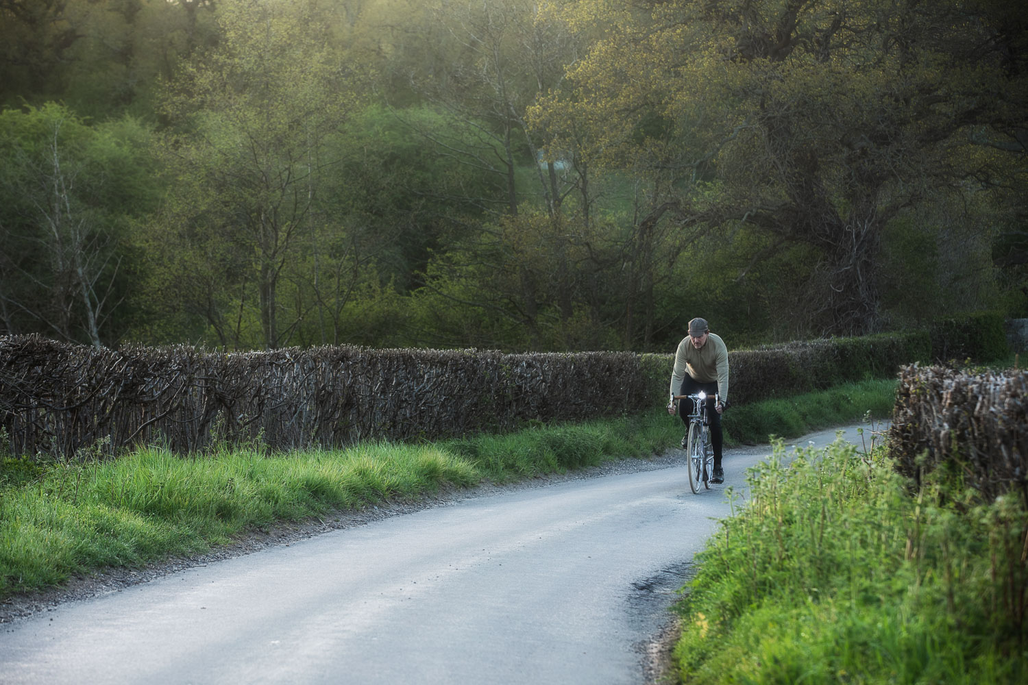 Cyclist pedalling along pretty English country lane