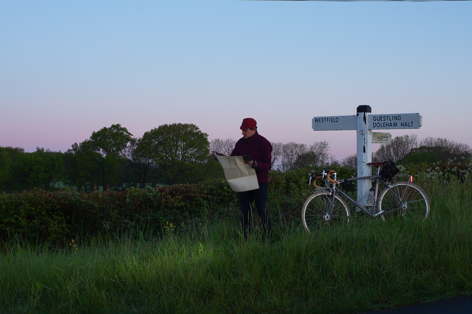 Cyclist consulting map by old wooden signpost