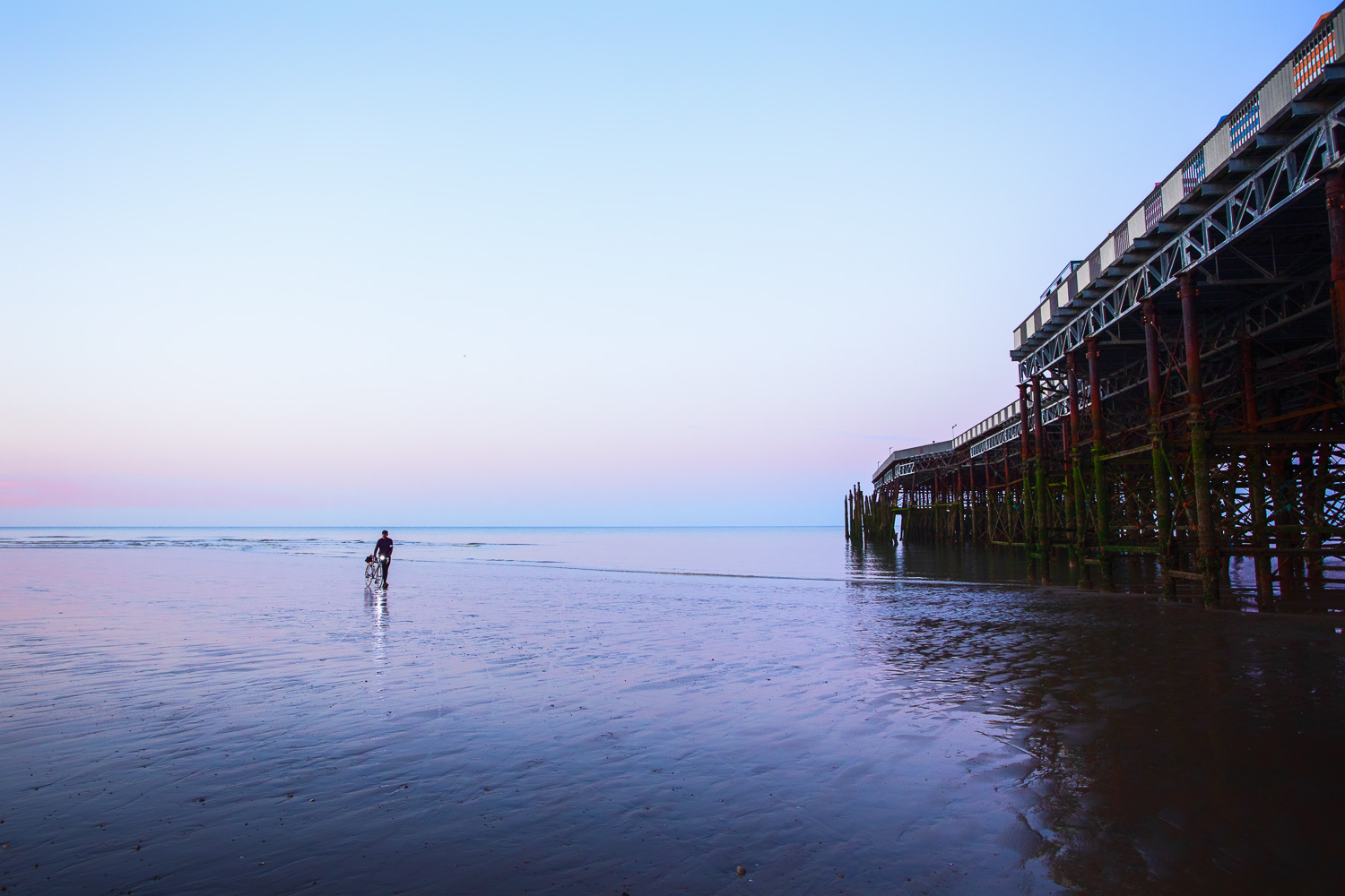 Man with bicycle walking on shimmering beach sands at dawn by pier