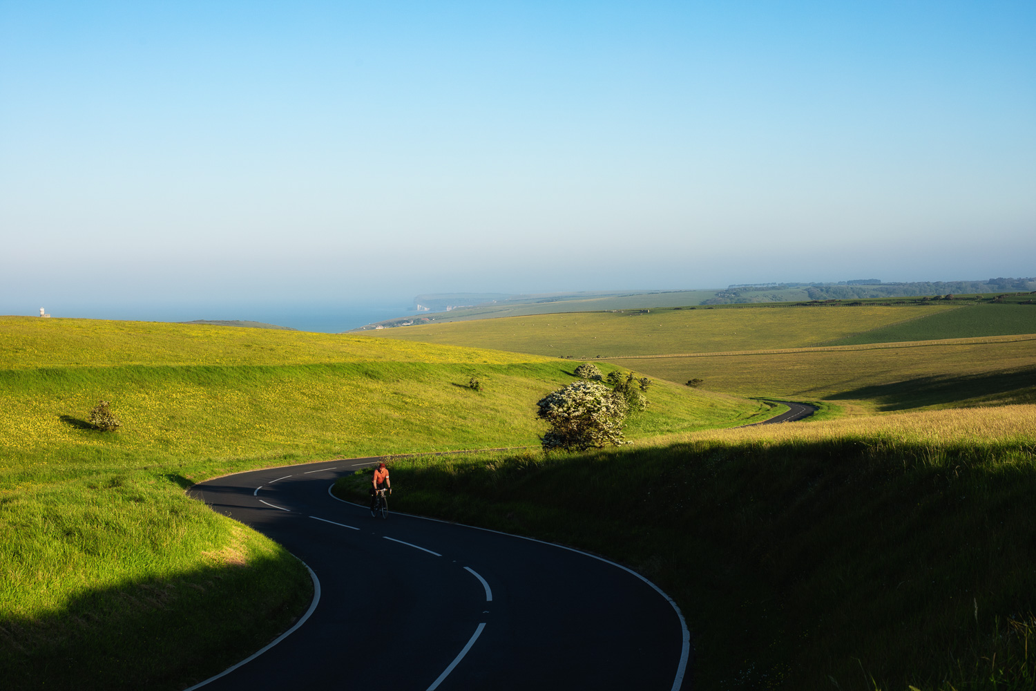 Cyclist on long winding road with distant view of English coastline