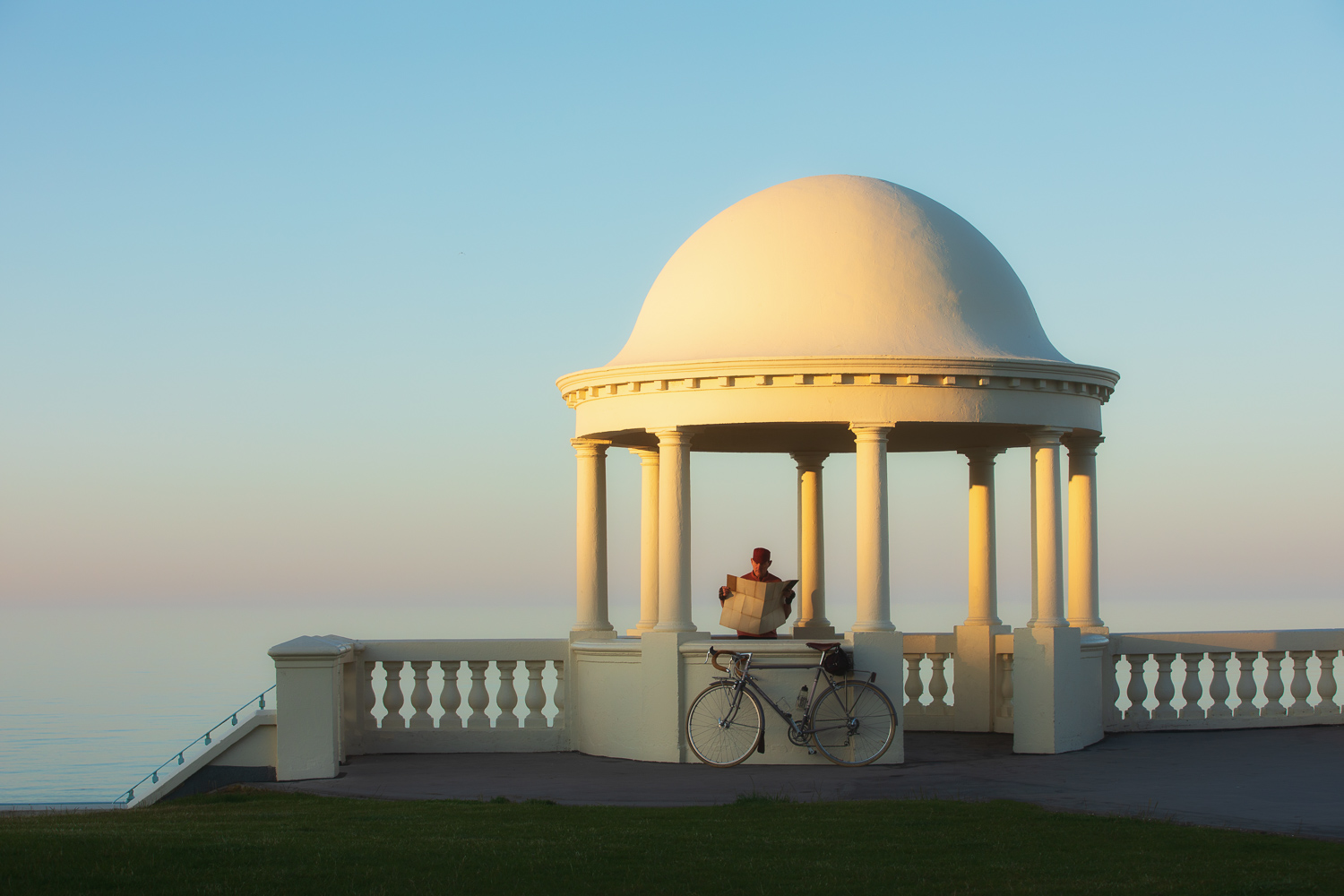 Man with bicycle reading map under classical dome