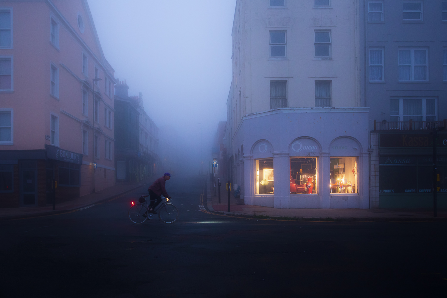 Cyclist on deserted city street at night in fog