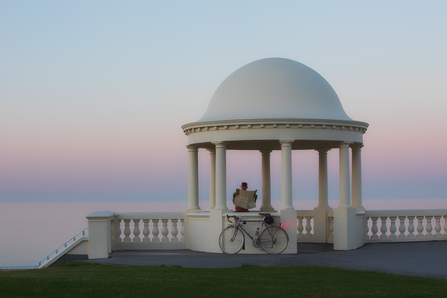 Man with bicycle in elegant dome looking at sea at dawn