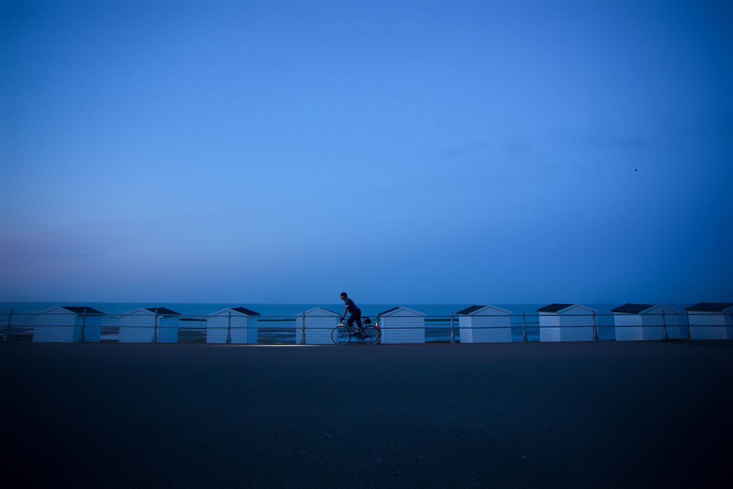 Lamp-lit cyclist pedalling past row of beach huts in blue twilight