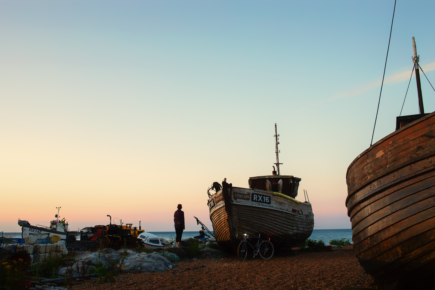 Man with bicycle beside old fishing lugger at dawn