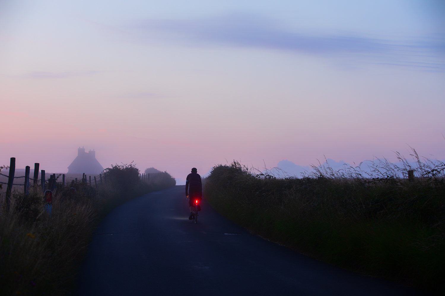 Cyclist pedals up hill on country lane just before dawn