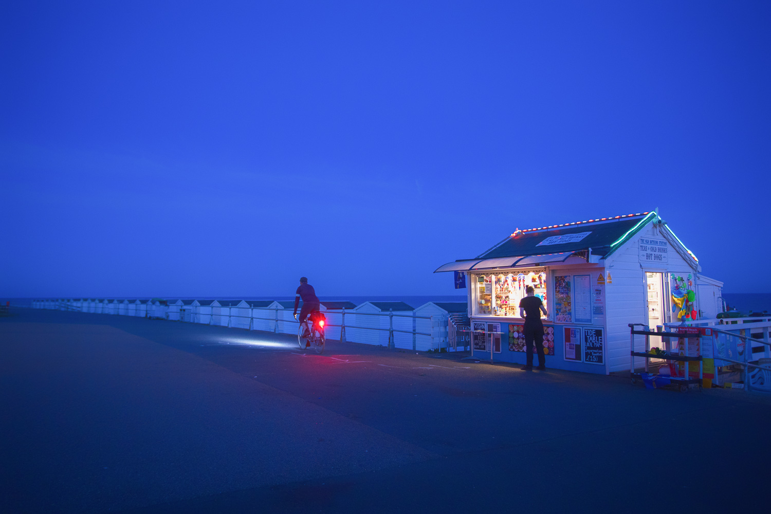 Cyclist pedals past ice cream kiosk on deserted promenade at dusk