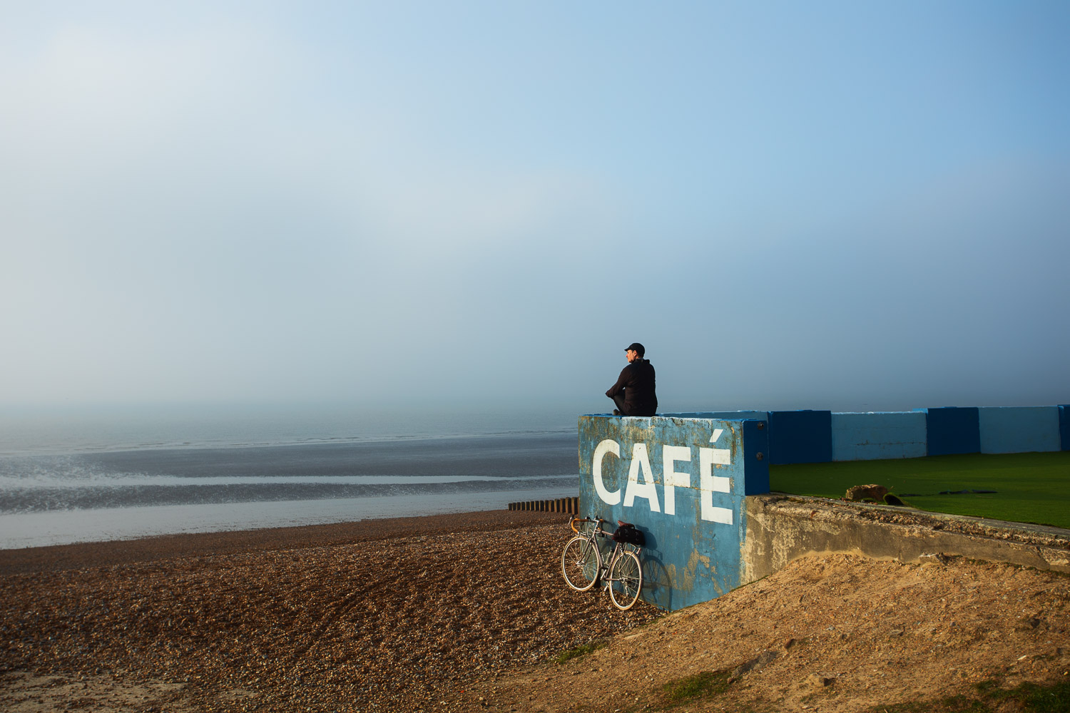 Cyclist sitting on sea wall beside bike looking out to sea