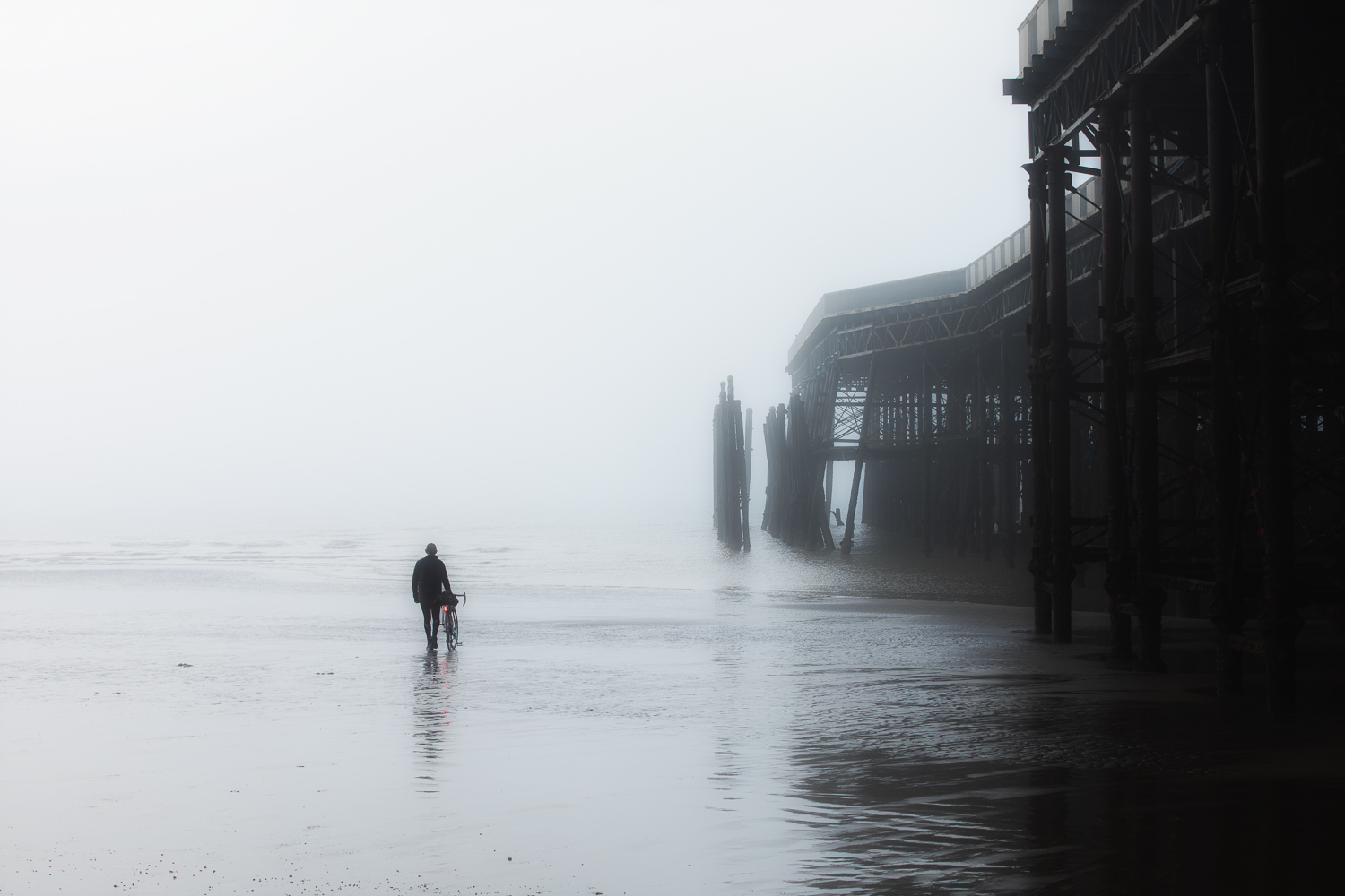 Monochrome of man with bicycle in mist beside footings of old pier