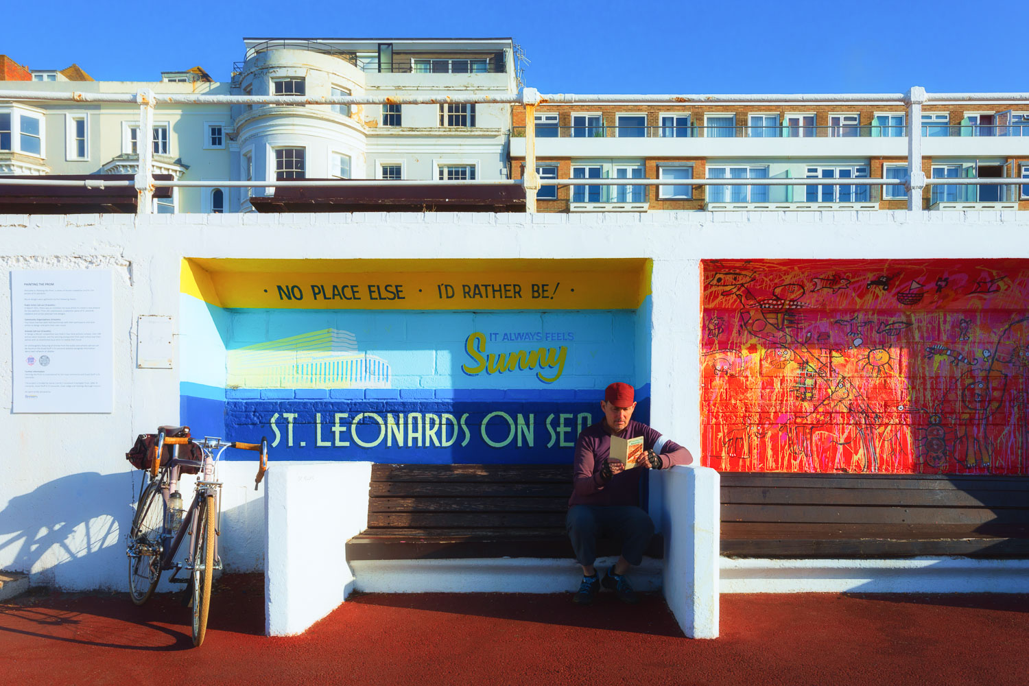 Cyclist looking at map by mural on the seaside