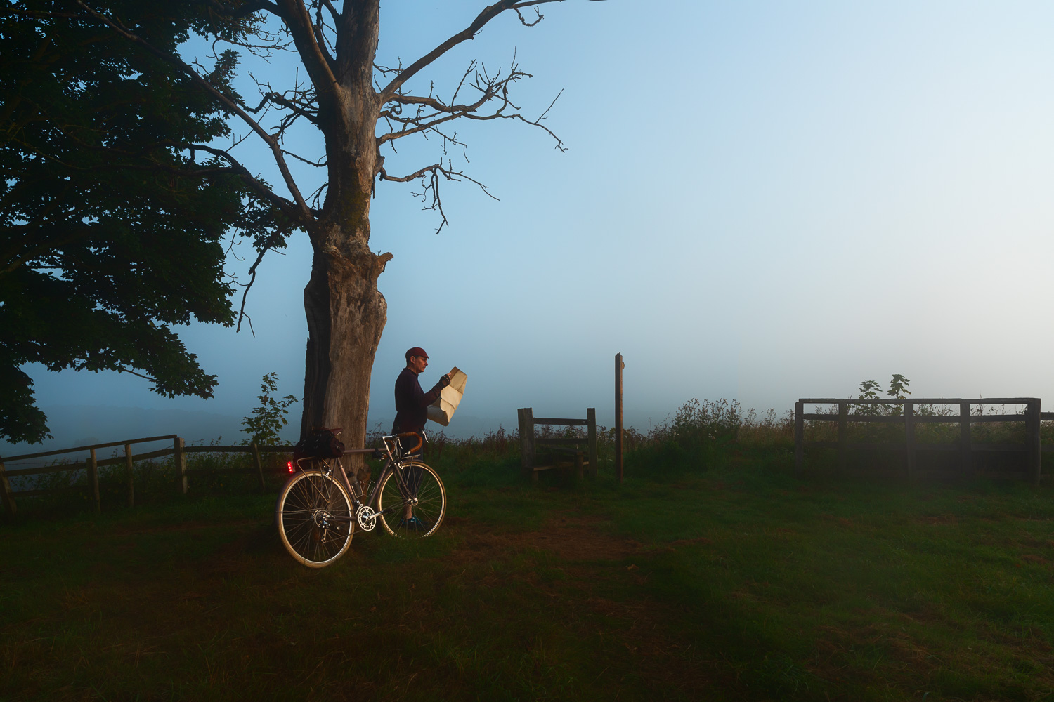 Cyclist looking at map at sunrise on country road