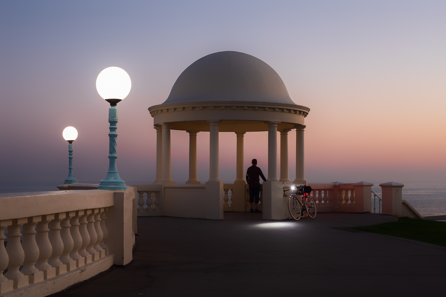 Man with bicycle looking out to see at twilight by classical colonnade